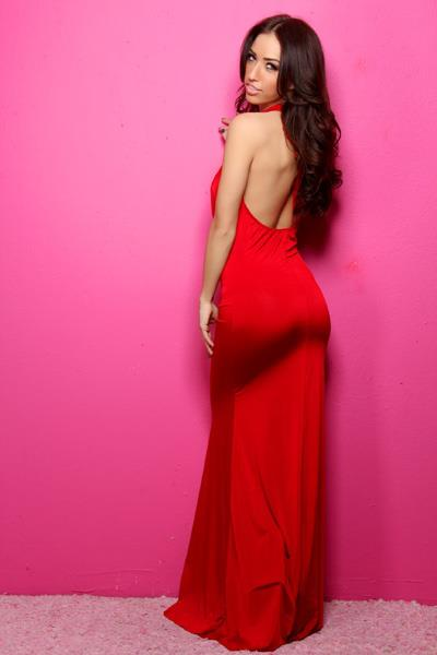 Bre Tiesi looking back seductively at the camera while wearing a long and tight fitting red dress