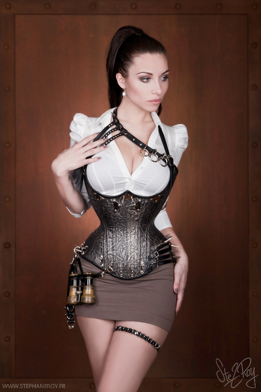 stunning steampunk woman with brown hair wearing a tight metal corset and a very short skirt
