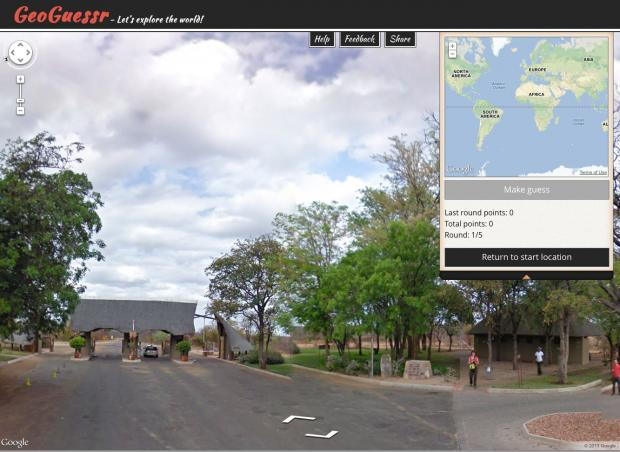 a picture from geoguessr.com depicting an entrance to some kind of national park or resort. there are many trees and clouds.