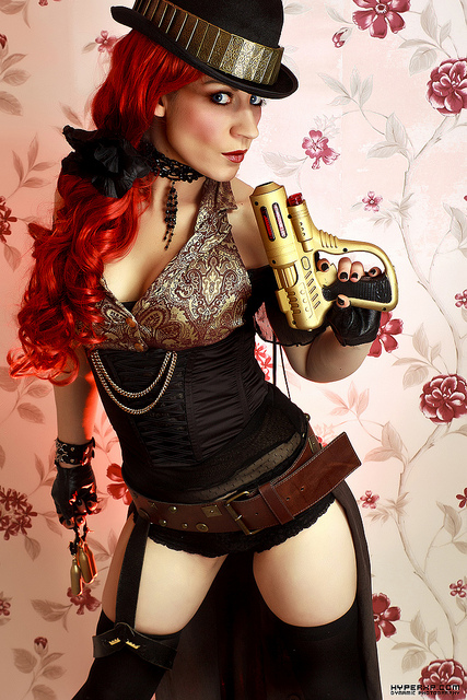 steampunk babe with red hair wearing a bowler derby hat. She is wearing a silver, gold, and black, corset and short underwear with black tights. She is holding a futuristic pistol and looking away from the camera
