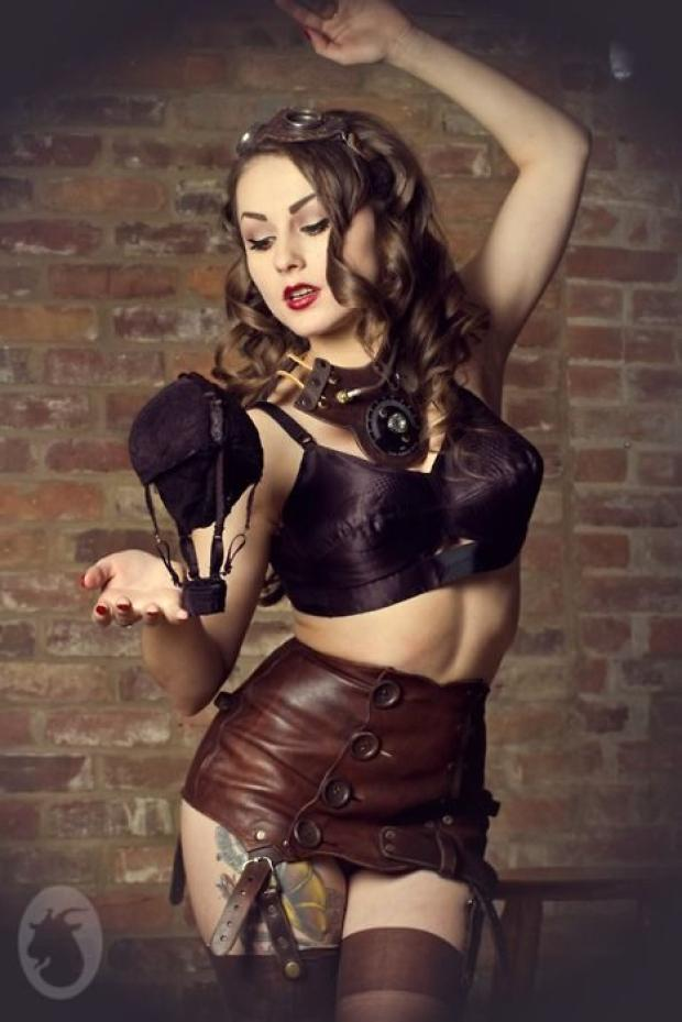 dancing brown haired steampunk woman in a brown leather bikini top and a short brown leather skirt