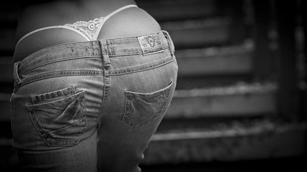 black and white photo of woman in thong pulled higher than her jean shorts